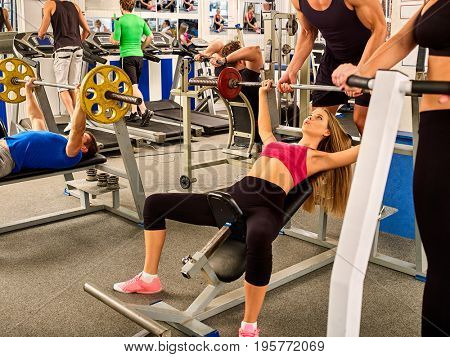 Fitness friends workout gym. Woman working on bench press. She lifting barbell. Trainer backs girl while taking exercises. Group work people on treadmill background. Girl wants to look sportive idea.