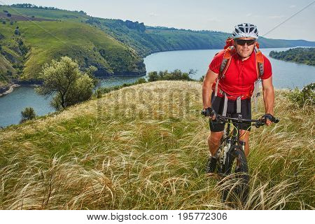 Cyclist has adventure on his mountain bike through green meadow against beautiful sky. Attractive sportsman in the black sportwear, with helmet and backpack. Healthy and active lifestyle concept
