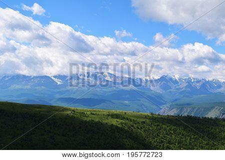 White peaks of North-Chuysky ridge and green meadows of Kurai steppe in Altai mountains. Altay Region Siberia Russia.