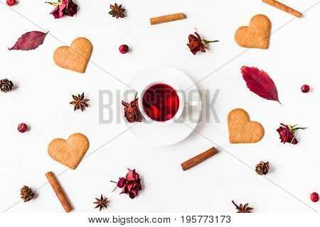 cup of fruit tea with autumn leaves cookie cinnamon sticks star anise cones dry roses top view flat lay