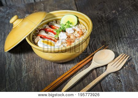 Thai spicy instant noodle with shrimps and boiled egg on wood background