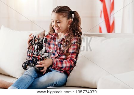 Relax at home. Joyful kid keeping smile on her face and bowing head while playing with robot