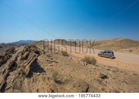 Car On Gravel Road In The Namib Desert, Namib Naukluft National Park, Main Travel Destination In Nam