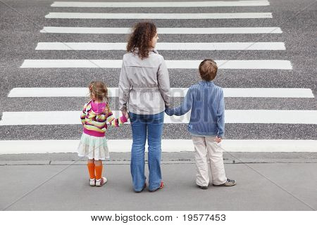 young mother holds hand of his little daughter and son and standing near cross road, behind