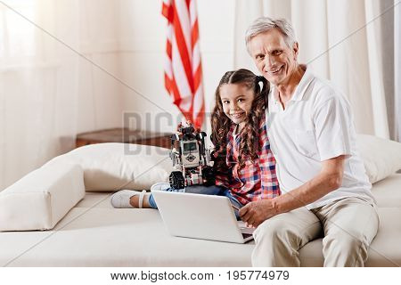 Just relax. Pretty brunette girl expressing positivity while spending weekend with her grandfather, holding robot in right hand