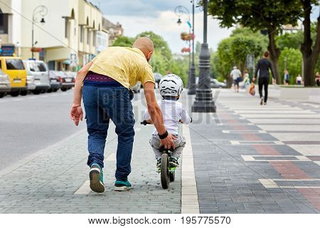 First lessons bicycle riding. Father teach his son to ride a bike. Happy childhood concept