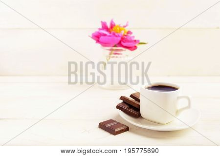 A Cup Of Coffee With Chocolate And One Flower In Vase On White Background