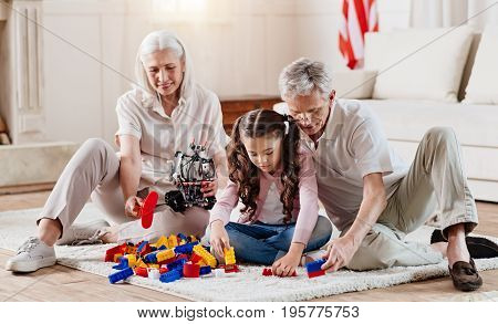 Playing at home. Attentive kid crossing legs and bowing head while sitting on the floor with her grandparents