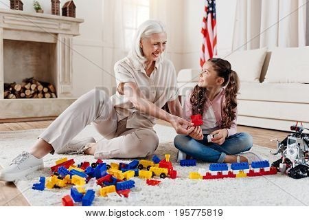 Interesting task. Charming lady keeping smile on her face and holding toy while sitting near her granddaughter