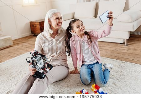 Pose on camera. Positive delighted girl keeping smile on her face and raising left arm with gadget while sitting on the floor