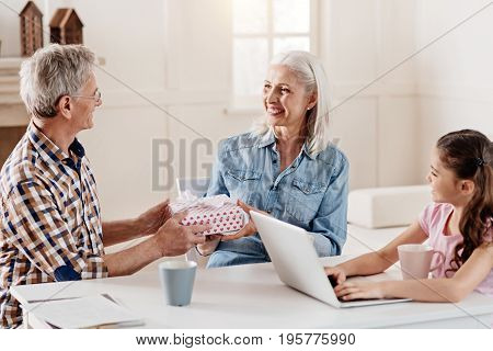 Present for you. Attentive girl keeping smile on her face and holding hands on computer while looking at her grandparents
