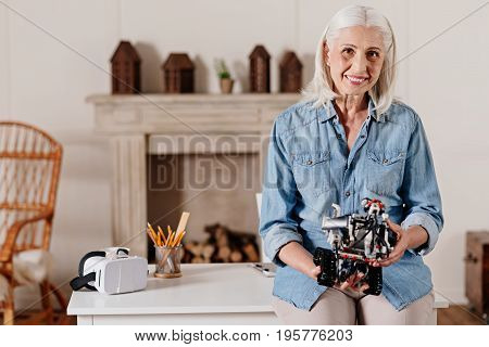 Positive thoughts. Delighted mature woman being at home keeping smile on her face while holding robot in both hands