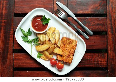 A plate of french fries with catchup Wooden background.