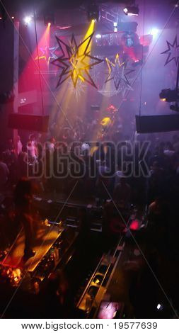 Nightclub scene with christmas decor, dancer and dance floor crowd in motion