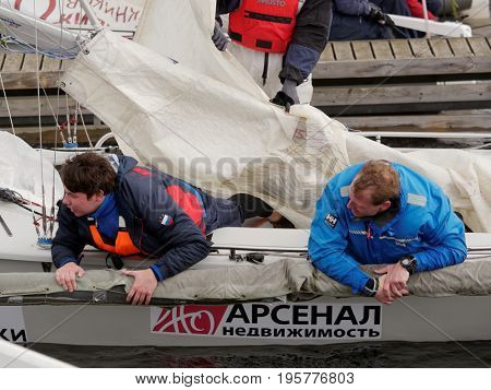ST. PETERSBURG, RUSSIA - JUNE 27, 2017: Athletes lowering their sails after the final of Saint Petersburg University Open Cup. It's the only students' sailing regatta in the city