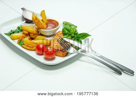 Fried Seasoned Potato Wedges with Cherry Tomatoes on Vine and Fresh Basil Herbs on White Background
