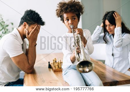Picture of child making noise by playing trumpet in front of parents