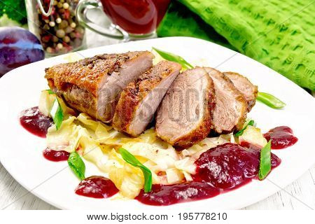 Fried duck breast with stewed cabbage, green onions and plum sauce in a white plate, towel, on a wooden plank background