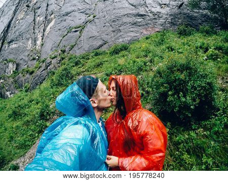 Guy and girl tourists are happy, hug and do selfie on action camera on background of mountains, forests raincoat in rain. Concept kiss and travel. Russia, Altai Mountains.