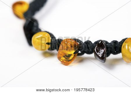 Bracelet made of amber beads and black cord close up on white background.