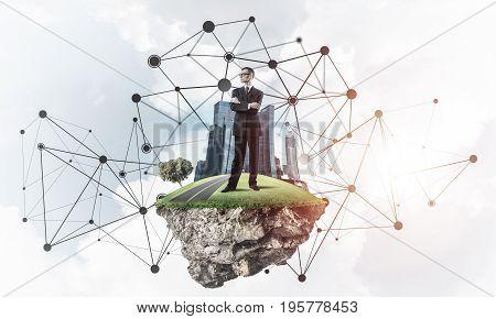 Elegant businessman on flying green island floating in blue sky