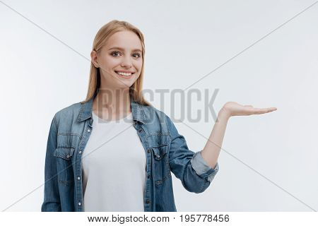 Look here. Pretty woman with enigmatical smile looking straight at camera and holding left palm up while standing isolated on white background