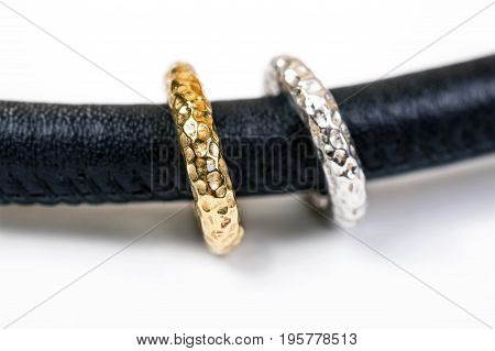 Modern leather neсklace with gold and silver rings on white background