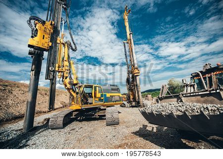 Highway Construction Site With Heavy Duty Machinery. Two Rotary Drills, Bulldozer And Excavator Work