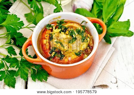 Fish baked in tomato in Zandvoort in red ceramic pot on a napkin, parsley and basil on a wooden boards background