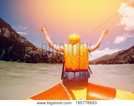 man sits on the edge of a rafting boat in rescued jelly and a protective helmet, rejoices, raises his hands up, rear view. Concept of active summer. Glare sun