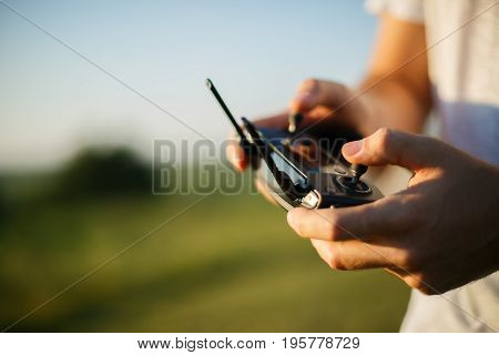 Man holds a drone remote controller in his hands. Close-up of quadcopter RC with antennas during flight. Pilot takes aerial photos and videos with quad. No face poster
