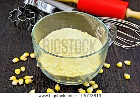 Flour corn in a glass cup, grain, rolling pin and metal cookie cutters on a wooden board
