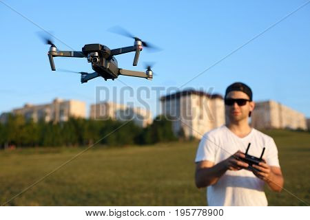 Compact drone hovers in front of man with remote controller in his hands. Quadcopter flies near pilot. Guy taking aerial photos and videos