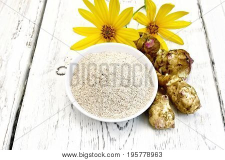 Flour of Jerusalem artichoke in a bowl with flowers and vegetables on the background of wooden boards