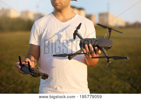 Happy man shows You small compact drone and remote controller. Pilot holds quadcopter and RC in his hands on sunset poster