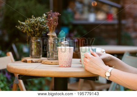 Woman's hands holding cup of coffee on table