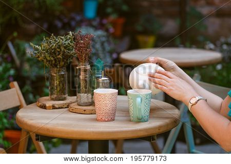 Person Fills Cup Of Tea In The Cafe