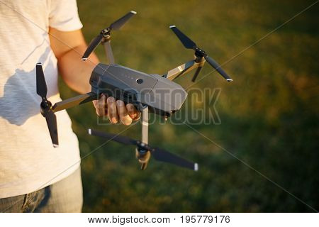 Happy man shows You small compact drone and remote controller. Pilot holds quadcopter and RC in his hands on sunset