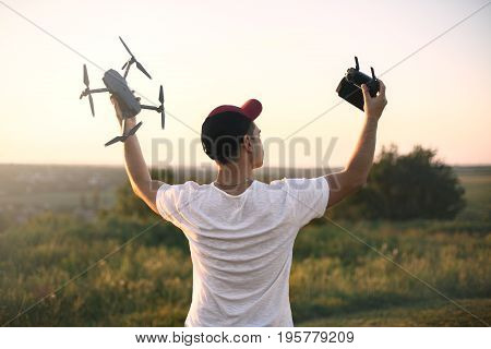 Silhouette of man holding drone quad copter and remote control enjoying freedom, victory, success on sunset. Business concept, hands up