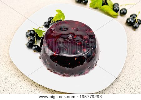 Jelly from a black currant with berries in a plate on a napkin on the background of a granite table