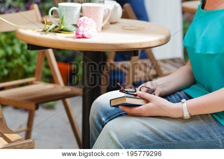 Woman Drinking Coffee And Reading Book In An Outdoor Cafe