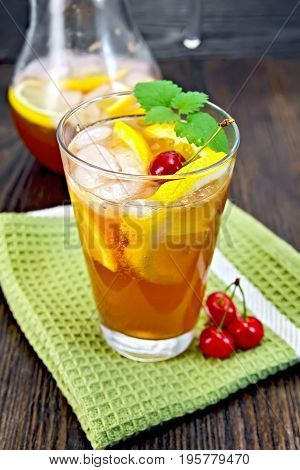 Lemonade in a glassful and jug with a cherry, lemon, orange and mint on a green towel on a wooden plank background