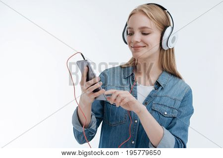 Listen to music. Attractive girl keeping smile on her face and looking downwards while using her gadgets, isolated on white