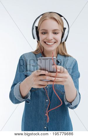 Modern technologies. Charming blonde wearing headphones and holding her device in both hands while standing over white background