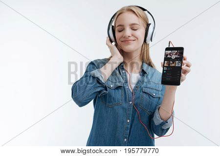 Song list. Dreaming girl keeping eyes closed while listening to music, putting right hand on the headphones