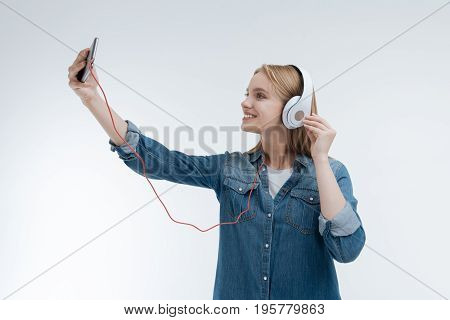 Selfie time. Charming young woman raising her right arm and touching her headphones while looking at mobile telephone