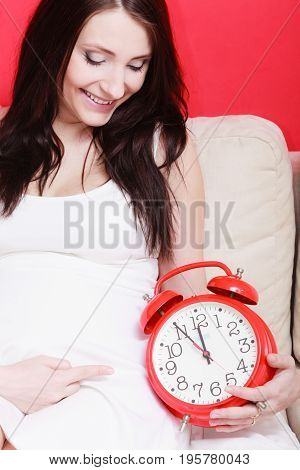 Pregnancy motherhood expecting concept. Pregnant woman holding big red old fashioned clock waiting for childbirth