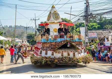 CHIANGMAI THAILAND - JANUARY 25 2015: Indigenous women with traditional costume holding red paper umbrella on decorated vehicle with flowers and bamboo basket in parade of 22nd Traditional Skirt Fabric and The Indigenous Product and Culture Festival in Ma