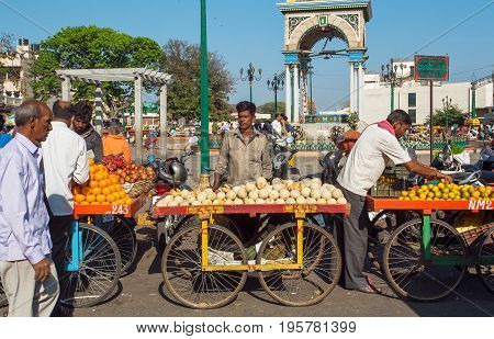 MYSORE, INDIA - FEB 18, 2017: Fruits and vegetables traders selling melons and mandarins on busy street market on February 18, 2017. Mysore of Karnataka has a population of 900000