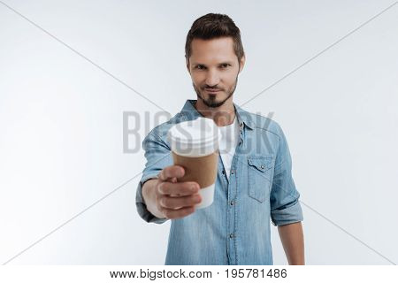 You may take it. Enigmatical male person pressing lips and looking forward while standing over white background